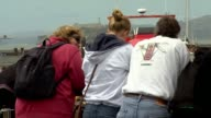 Shots of tourists at Fisherman's Wharf in San Francisco on July 17 A wide shot of tourists looking out over the bay with a boat in the background A...