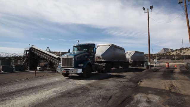 Shots of Trucks hauling multiple 40ton trailers from the coal mines to a transport train station Close ups of the 40ton truck trailers dumping coal...