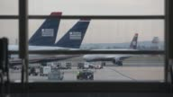 Shots of US Airways airplanes from inside an airport terminal at Ronald Reagan National Airport in Washington DC Passengers carrying luggage walk...