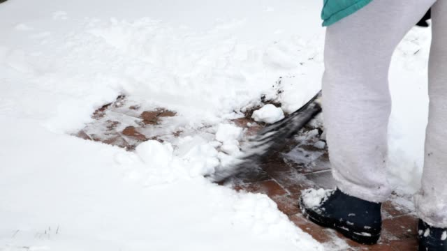 Shoveling Snow on Brick Sidewalk