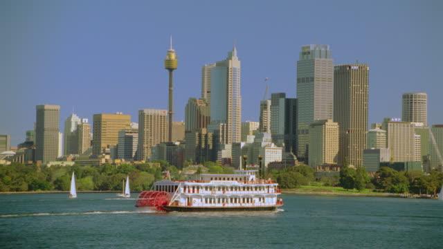 'Showboat II' riverboat travelling through harbor near Sydney city skyline / Sydney, Australia