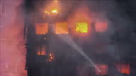 Shows aerial and exterior shots blackened shell of Grenfell Tower and damage to building after the fire was put out Exterior shots fire crews aiming...