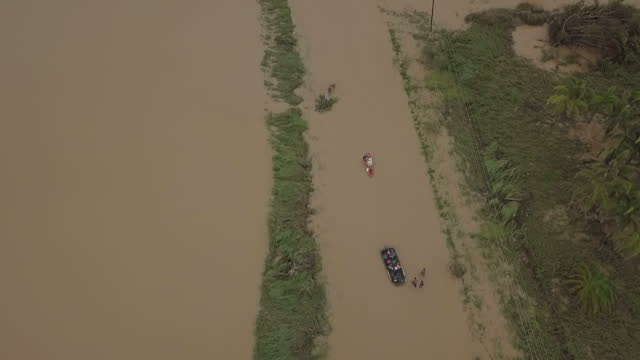 Shows aerial drone shots approaching heavily flooded area around Toa Bah and people rescuing residents and belongings in boats and wading through...
