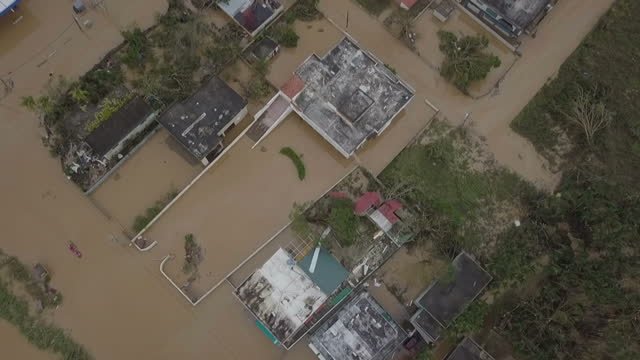 Shows aerial drone shots birds eye shot flying over flooded houses and residential neighbourhood in Toa Baha 15 people are known to have died and 20...