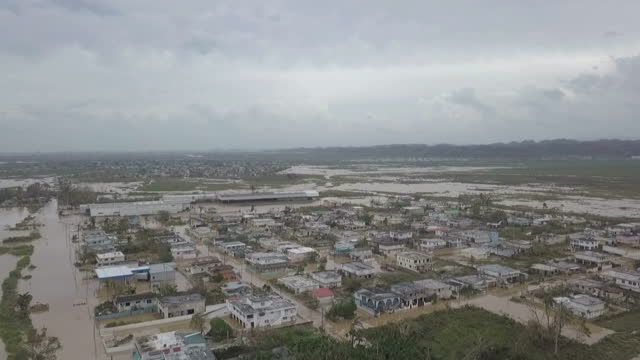 Shows aerial drone shots flooded houses in residential neighbourhood in Toa Baha 15 people are known to have died and 20 more are missing after...
