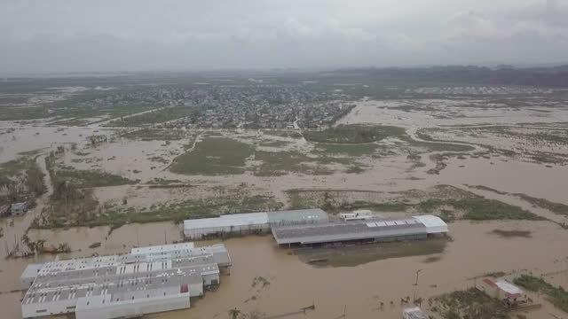 Shows aerial drone shots flying over flooded landscape and residential houses in Toa Baha 15 people are known to have died and 20 more are missing...