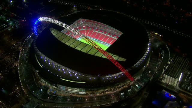 Shows Aerial night shots Wembley stadium in London lit up in red white and blue colours of the French flag with fans making way into the Stadium and...
