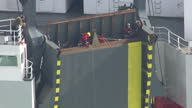 Shows aerial shots Greenpeace activists tying themselves onto ramp at rear of cargo ship vehicle carrier Elbe Highway at sea Protesters from...
