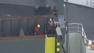 Shows aerial shots Greenpeace activists tying themselves to access ramp at rear of cargo ship vehicle carrier Elbe Highway at sea Protesters from...