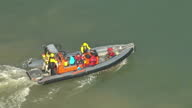 Shows aerial shots pan from Greenpeace activists in dinghy in wake of cargo ship vehicle carrier Elbe Highway to police officers in different dinghy...