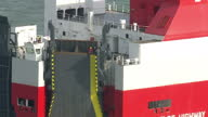 Shows aerial shots pan into Greenpeace activists on top of ramp at rear of cargo ship vehicle carrier Elbe Highway at sea Protesters from Greenpeace...