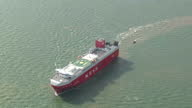 Shows aerial shots pan out from police officers in dinghy to show cargo ship vehicle carrier Elbe Highway at sea pan round and into Greenpeace...