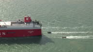 Shows aerial shots panning round cargo ship vehicle carrier Elbe Highway at sea with Greenpeace activists and police officers in dinghys behind the...