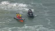 Shows aerial shots police officers in dinghy circling Greenpeace activists in their own dinghy following cargo ship vehicle carrier Elbe Highway at...
