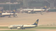 Shows aerial shots Ryanair plane taxiiing on runway and near terminals at Stansted Airport with passengers walking to plane in background Ryanair's...