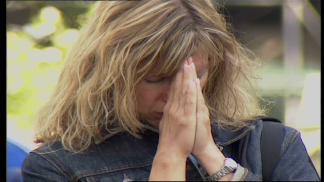 Shows exterior closeup shot of women praying for victims of 9/11 on September 16 2001 in New York City