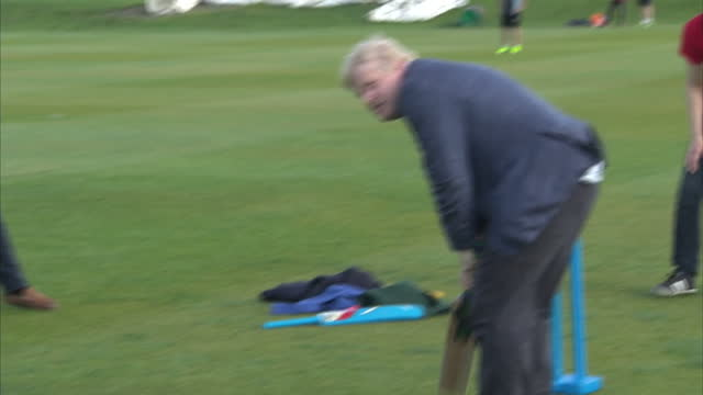 Shows exterior hots Conservative MP and 'Out'Campaigner Boris Johnson playing cricket batting hitting cricket balls with group of teenagers at a Vote...