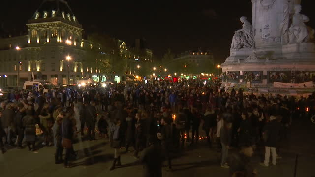 Shows Exterior night shots crowds gathered in Place de la Republique for candle lit vigil for victims of Friday Night's terror attacks France has...