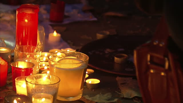 Shows Exterior night shots people crouched down lighting candles and arranging tributes left to victims of terror attacks outside the Bataclan cafe...