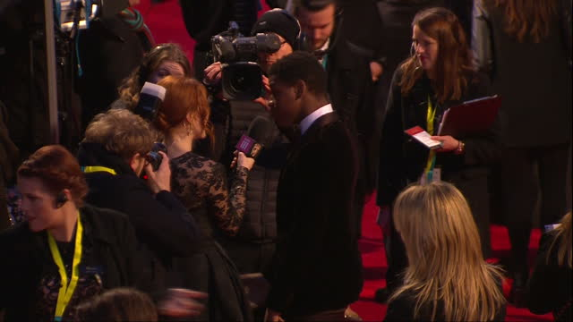 Shows Exterior shots actor John Boyega being interviewed on red carpet and walking through crowd to talk to fans The 2016 BAFTAS Film Awards ceremony...