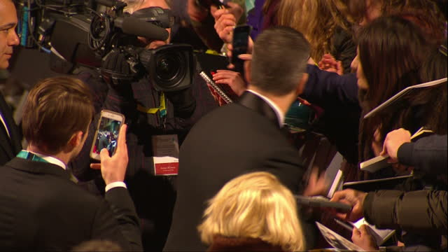 Shows Exterior shots actor Matt Damon signing autographs on red carpet The 2016 BAFTAS Film Awards ceremony at was held at London's Royal Opera House...