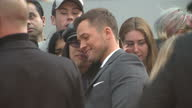 CLEAN Shows exterior shots actor Taron Egerton signing autographs and posing for selfies with fans on the orange carpet at the World Premiere of...