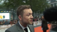 CLEAN Shows exterior shots actor Taron Egerton talking to press on the orange carpet at the World Premiere of 'Kingsman The Golden Circle' held at...