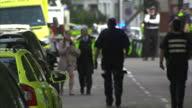 Shows exterior shots an injured woman with bandage wrapped around her head being escorted by a police officer away from Parson Green Tube Station and...