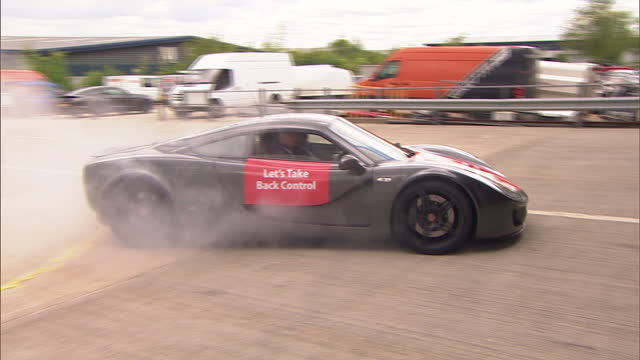 Shows exterior shots Boris Johnson taken for joyride in Ginetta Car with car doing donuts in car park and Vote Leave battle bus in background...