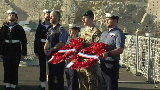 Shows Exterior shots British Prime Minister David Cameron and UK's Home Secretary Theresa May on board HMS Bulwark laying poppy wreaths during...