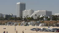 Shows exterior shots cars filling parking lot with Santa Monica beach in background and highrise buildings and beach front proerties overlooking the...