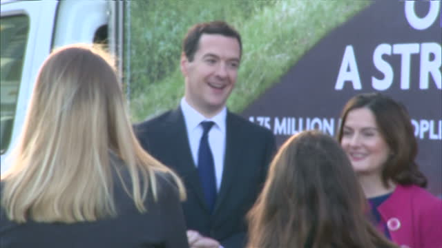 Shows exterior shots Chancellor George Osborne unveiling fleet of Conservative posters stating 'Let's Stay On The Road To A Stronger Economy' on...