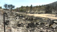 Shows exterior shots charred and twisted metal debris including gas canisters and burnt out caravans at campsite after wildfires destroyed the site...
