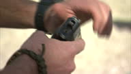 Shows exterior shots close ups man showing how to release the magazine on a handgun how to safely holster the weapon on October 16 2014 in Salt Lake...