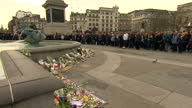 Shows Exterior shots Crowd of people gathering in Trafalgar Square London and holding a minute's silence at 11 o'clock for victims of the Paris...