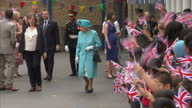 Shows exterior shots crowd of school children cheering and waving Union Jack flags as Queen Elizabeth II and Prince Philip depart Mayflower Primary...