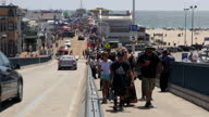 Shows exterior shots crowds of tourists filling pier and walking to and from the beach on hill leading down to beach and cars driving down hill...
