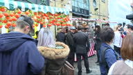 Shows exterior shots crowds of visitors and tourists at Camden Market in London including people watching crepes being cooked on food stall sitting...