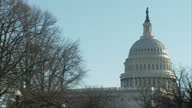 Shows exterior shots dome of United States Capitol building with close up of Statue of Freedom on top of dome and an airplane crossing sky behind the...