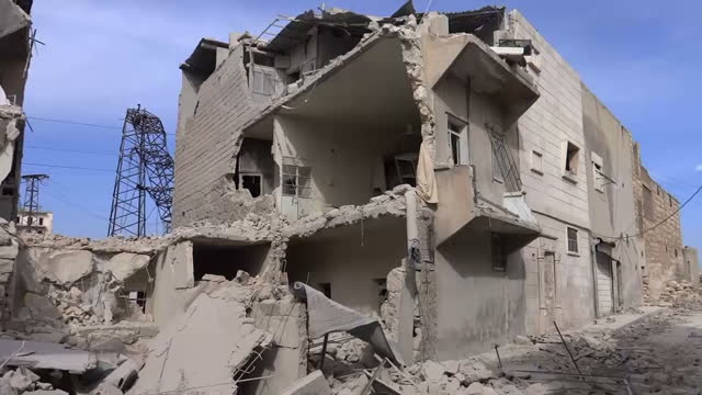 VOICED Shows exterior shots driving shots through Northern Syria with refugees in trailers heading towards Turkish Border and past abandoned crops in...