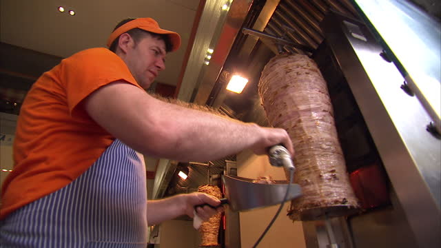 Shows exterior shots Evzones t shirts for sale man in kebab shop slicing meat on June 28 2015 in Athens Greece