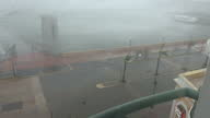 Shows exterior shots from hotel window strong winds as Hurricane Maria arrives in San Juan with waves throwing water across the road and palm trees...