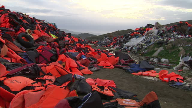 Shows exterior shots gravestones in graveyard for dead migrants in Lesbos Exterior shots Aegean Sea and shoreline with abandoned orange life jackets...