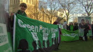 Shows exterior shots Green Party members activists standing with banners on College Green in the shadow of the Houses of Parliament on January 19...