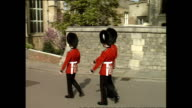 Shows exterior shots Guardsmen soldiers wearing bearskin hats and red coats marching down hill near St George's Chapel in Windsor Castle on April 19...