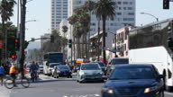 Shows exterior shots man wearing a viking helmet riding a bike through traffic in Santa Monica on 26th July 2017 in California USA