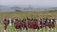 Shows exterior shots military marching band from a Highland Regiment playing music as naval officers stand waiting for ceremony to begin at Lyness...