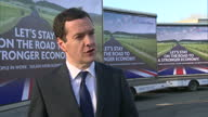 Shows exterior shots new conservative posters on trucks stating 'Let's Stay On The Road To A Stronger Economy George Osborne interview stating the...