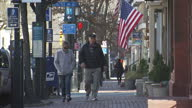 Shows exterior shots older couple walking down sidewalk underneath an American Flag on 13th February 2017 in Alexandria Virginia United States