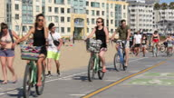 Shows exterior shots peopl eriding bikes skateboarding and jogging on track across Santa Monica Beach on 26th July 2017 in California USA